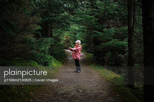 Girl enjoying walk in forest - p1166m2130825 by Cavan Images