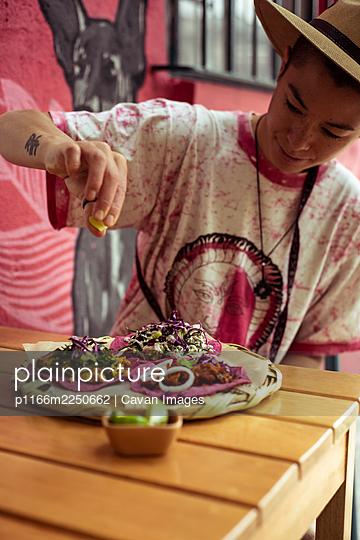 Alternative summer traveler dressing pink burritos in Mexico city - p1166m2250662 by Cavan Images