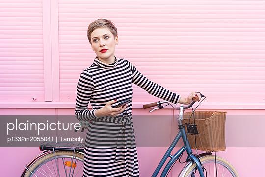 Blonde Frau mit Fahrrad und Mobilphone - p1332m2055041 von Tamboly