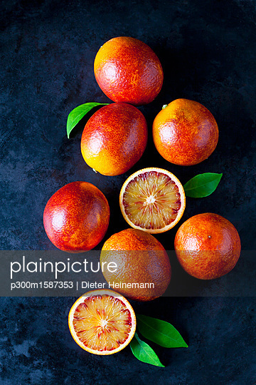 Whole and sliced blood oranges on dark ground - p300m1587353 von Dieter Heinemann