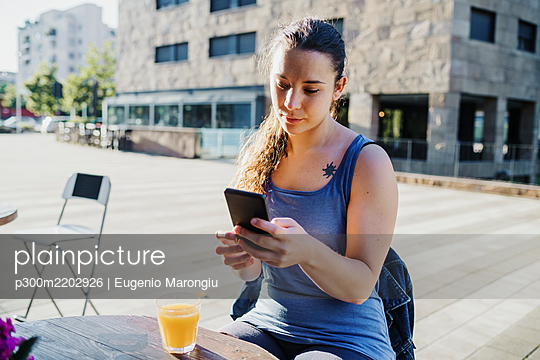Sporty young woman using smart phone while sitting at sidewalk cafe in city - p300m2202926 by Eugenio Marongiu