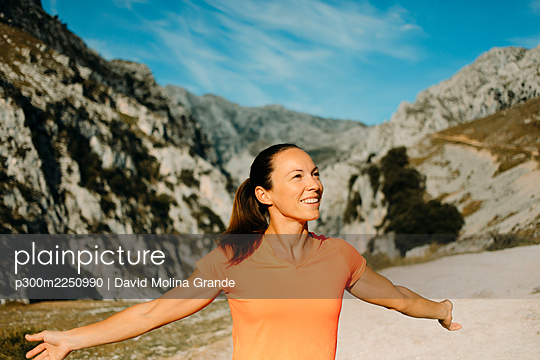 Carefree hiker smiling while standing with arms outstretched at Cares Trail in Picos De Europe National Park, Asturias, Spain - p300m2250990 by David Molina Grande