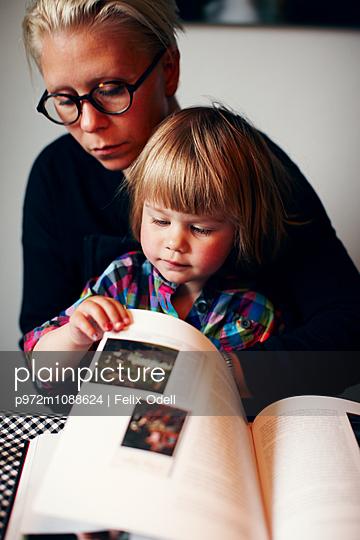 Mutter und Tochter blättern durch ein Buch - p972m1088624 von Felix Odell