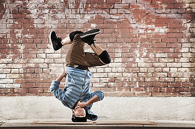 A young man doing a headstand, balancing on his head on a sidewalk. - p1100m1107165 by Mint Images