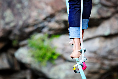 Low section of woman walking on rope against rocks - p1166m1094999f by Kyle Sparks