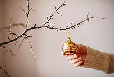 Cropped hand of woman touching bauble hanging on twig against wall during Christmas - p1166m1547027 by Cavan Images