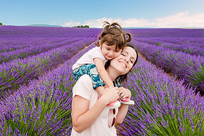 Happy woman and little girl walking among lavender fields in summer - p1166m2136659 by Cavan Images