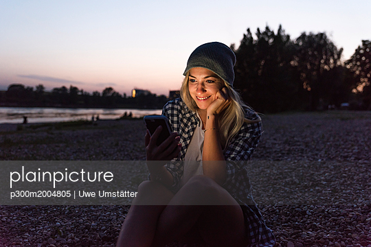 Young woman using smartphone on riverside in the evening - p300m2004805 von Uwe Umstätter