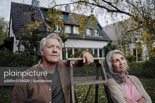 Senior couple with a ladder in garden of their home - p300m2155029 von Gustafsson