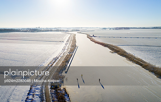 Nederland, Friesland, Broek, Aerial view of frozen canal and snow covered fields - p924m2283046 by Mischa Keijser