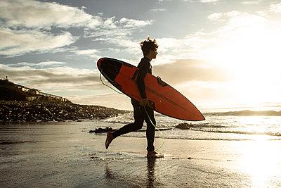Junger Mann mit Surfboard am Meer - p1640m2296018 von Holly&John