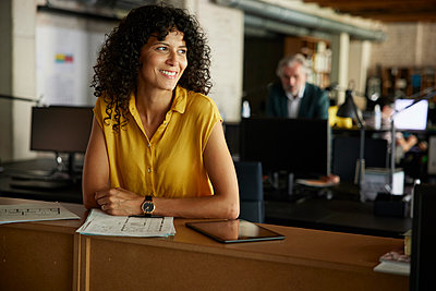 Smiling curly haired businesswoman with documents and digital tablet leaning on table at office - p300m2300424 by Rainer Berg
