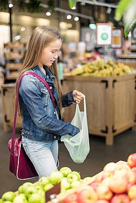 Girl buying apples in supermarket - p426m1407405 by Kentaroo Tryman
