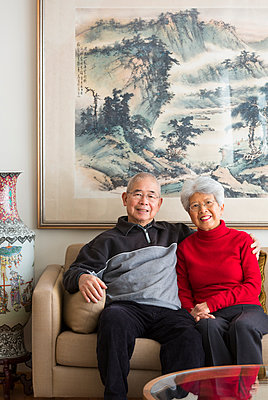 Chinese couple sitting on sofa - p555m1463670 by Don Mason