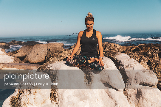 Young woman practises meditation on a rock by the sea - p1640m2261155 by Holly & John