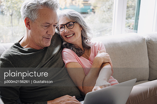 Happy senior couple with laptop relaxing on couch at home - p300m2156261 by Gustafsson