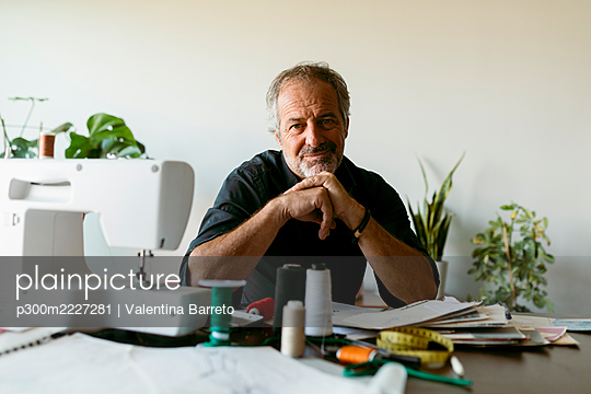 Smiling male tailor sitting at table against wall in work studio - p300m2227281 by Valentina Barreto