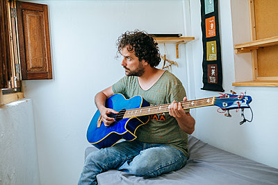 Spain, Man playing bass guitar in his room - p300m2012708 by Kiko Jimenez