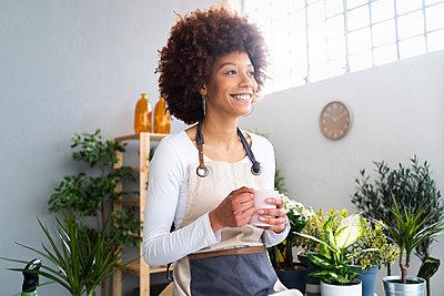 Afro woman gardening in a plant laboratory or shop, small business owner - p300m2287446 von Giorgio Fochesato