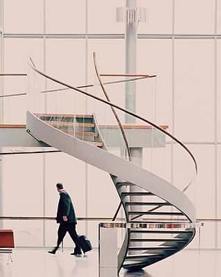 Modern spiral staircase in airport hallway - p312m714737 by Bruno Ehrs