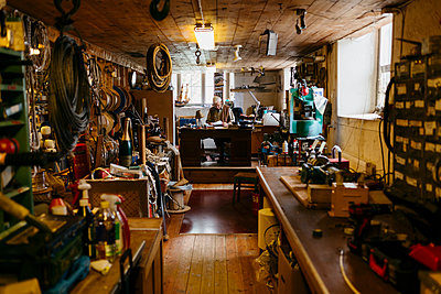 Rope maker sitting at desk in his shop - p352m2041166 by Folio Images