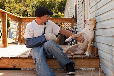 Man outside house with arm in sling and dog - p924m711235f by Raphye Alexius