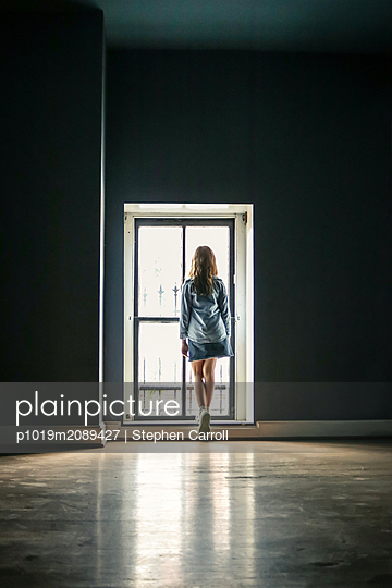 Girl jumping in empty room - p1019m2089427 by Stephen Carroll