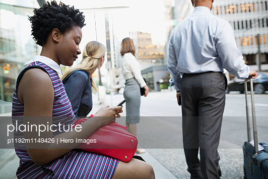 Business people waiting at city bus stop