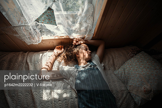 Girl sleeping on bed in the sunshine - p1642m2222232 by V-fokuse