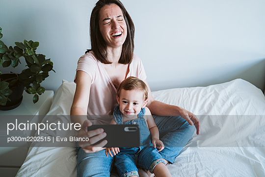 Mother and baby girl taking a selfie with smartphone at home - p300m2202515 by Eva Blanco
