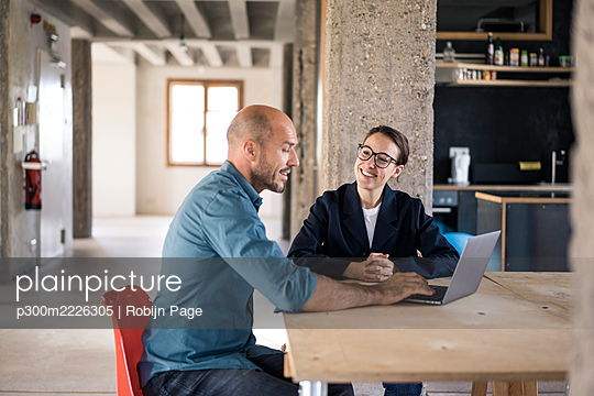 Business people discussing while using laptop at office - p300m2226305 by Robijn Page