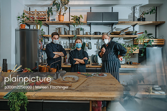 Confident chef wearing protective face mask staring while standing at kitchen - p300m2256900 by Mareen Fischinger