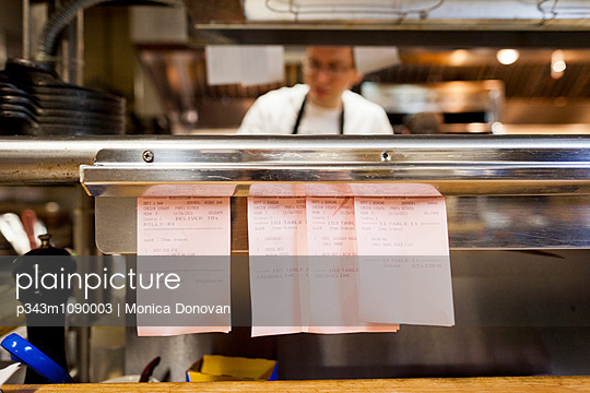 Cook and detail of restaurant order ticket slips in kitchen. - p343m1090003 by Monica Donovan