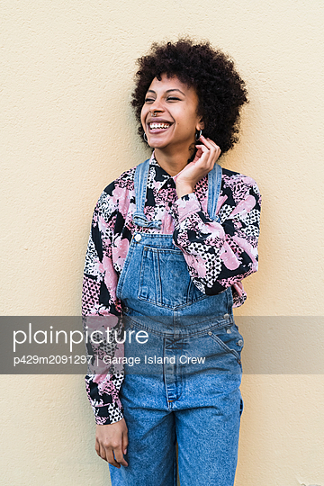Happy young woman in dungarees standing in front of wall, portrait - p429m2091297 by Garage Island Crew