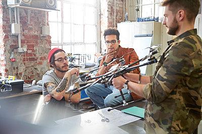 Designers meeting, examining drone in workshop - p1023m1486407 by Agnieszka Olek