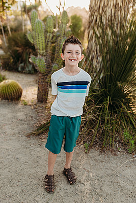 Full body view of young elementary aged boy smiling at camera outside - p1166m2136653 by Cavan Images