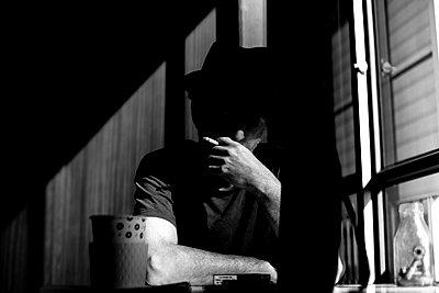 A smoking man sits by the window - p1484m2150264 by Céline Nieszawer