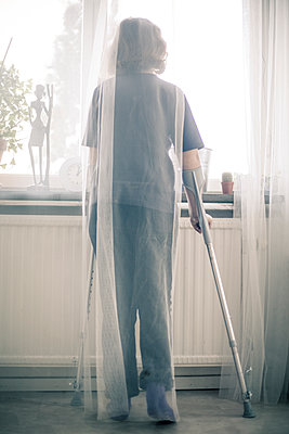 Girl with crutches looking out of the window - p1687m2295125 by Katja Kircher