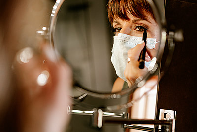 Woman applying make-up wearing protective face mask during COVID-19 - p300m2250396 by Albert Martínez