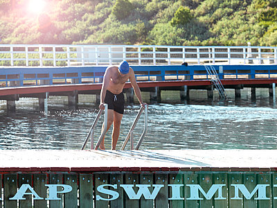 Swimmer coming up from water on ladder, Eastern Beach, Geelong, Victoria, Australia - p429m1418301 by Elke Meitzel