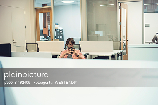 Man working in office, looking at smart phone