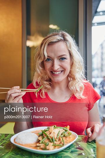 Portrait of smiling blond woman eating vegetarian Asian dish - p300m2013007 von Rainer Holz
