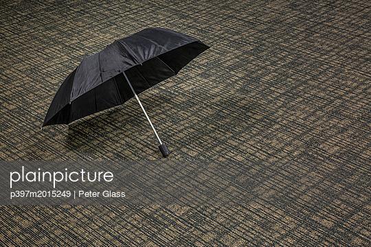 Offener Regenschirm auf einem Teppich - p397m2015249 von Peter Glass