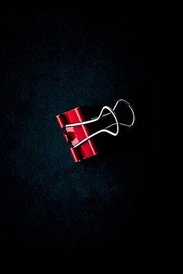 Red holdback paper clip on black background - p1302m2244359 by Richard Nixon