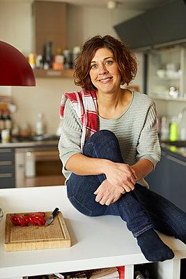 Portrait of smiling mature woman in the kitchen - p300m1587826 von Philipp Nemenz