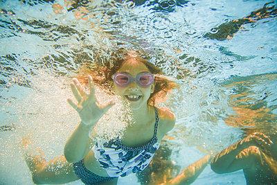 Caucasian girl swimming underwater in swimming pool - p555m1411536 by John Fedele