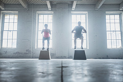 Silhouette of athletes jumping on platforms - p555m1411987 by John Fedele