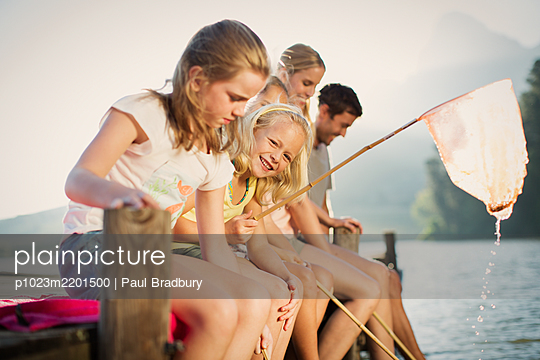 Family with fishing nets on dock over lake - p1023m2201500 by Paul Bradbury
