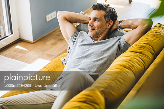 Man looking away while relaxing on sofa at home - p300m2294209 by Uwe Umstätter
