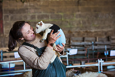 Woman standing in a barn, holding a newborn lamb dressed in a knitted jumper. - p1100m1450944 by Mint Images